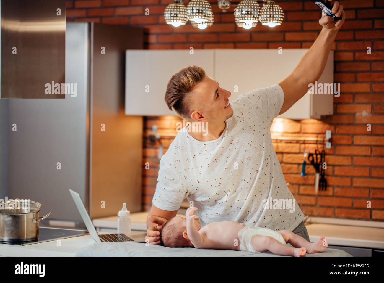 father are spending time with baby. Dad is doing selfie using a smartphone - Stock Image