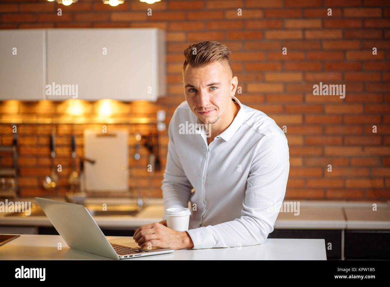 entrepreneur sitting in his office holding cup of coffee smiling to camera - Stock Image