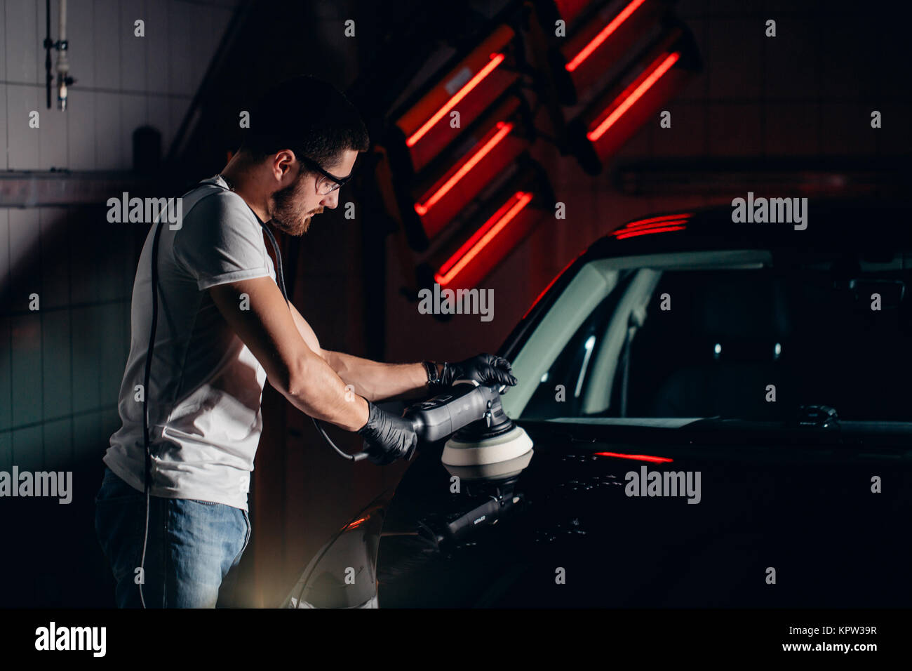 Car detailing - man with orbital polisher in auto repair shop. Selective focus. Stock Photo