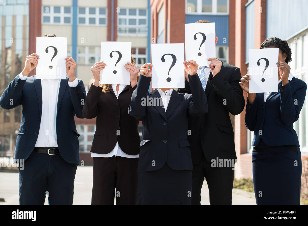 Businesspeople Hiding Face Behind Question Mark Sign - Stock Image