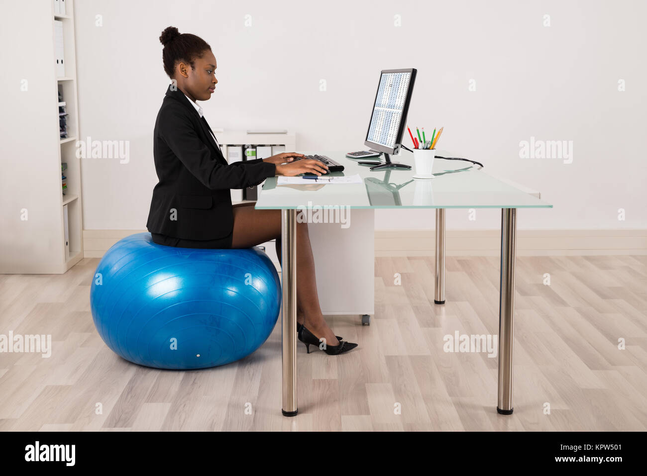 Businesswoman Sitting On Fitness Ball In Office - Stock Image