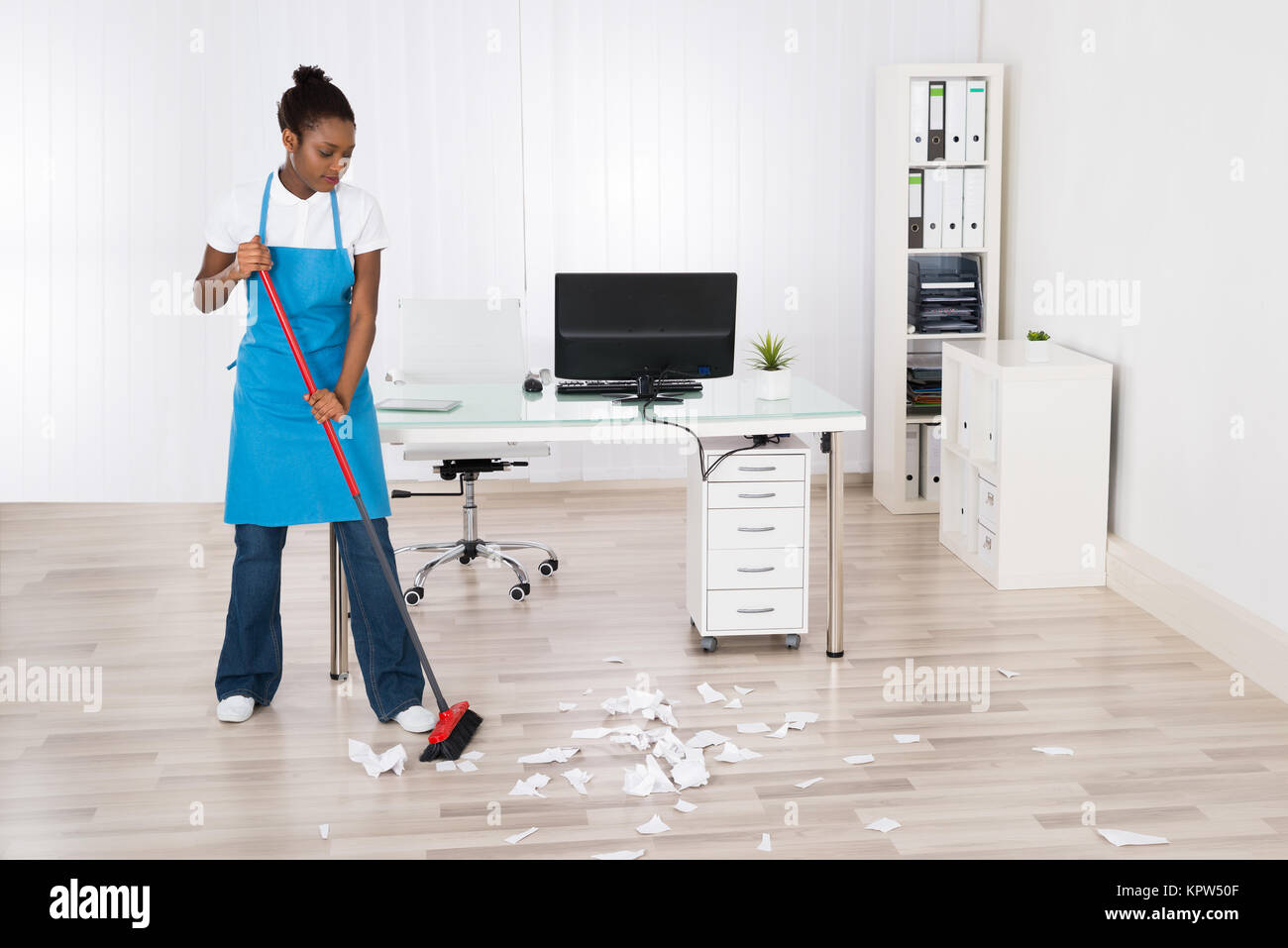 Female Janitor Sweeping Hardwood Floor - Stock Image