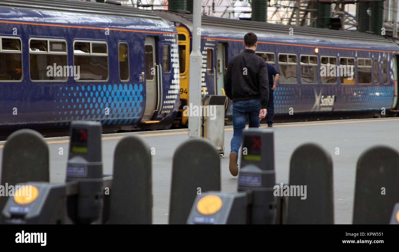 Ticket barriers, train and commuter on the platform at Glasgow Central train station, Glasgow, Scotland - Stock Image