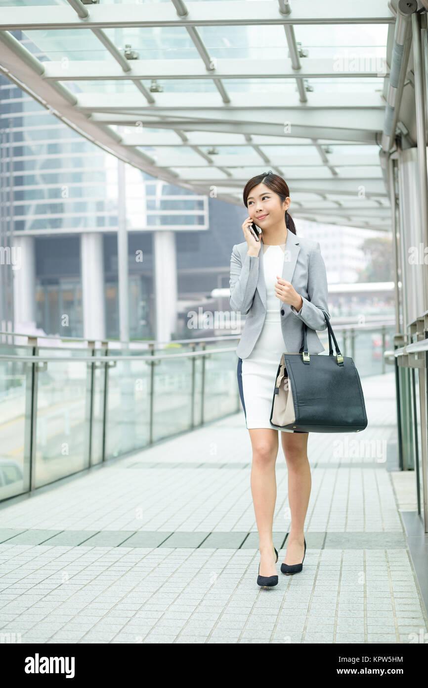 https://c8.alamy.com/comp/KPW5HM/business-woman-walking-outside-in-hong-kong-KPW5HM.jpg