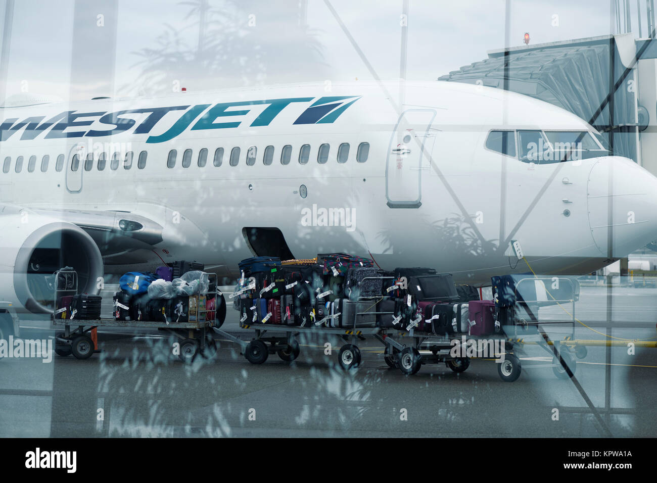 Artistic photo of a Luggage carrier train full of baggage about to be loaded on a WestJet airplane at a Victoria - Stock Image