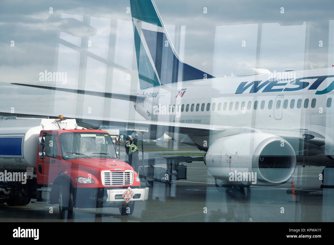 Artistic photo of fuel tanker track refueling WestJet airplane before a flight at a Victoria International airport, - Stock Image