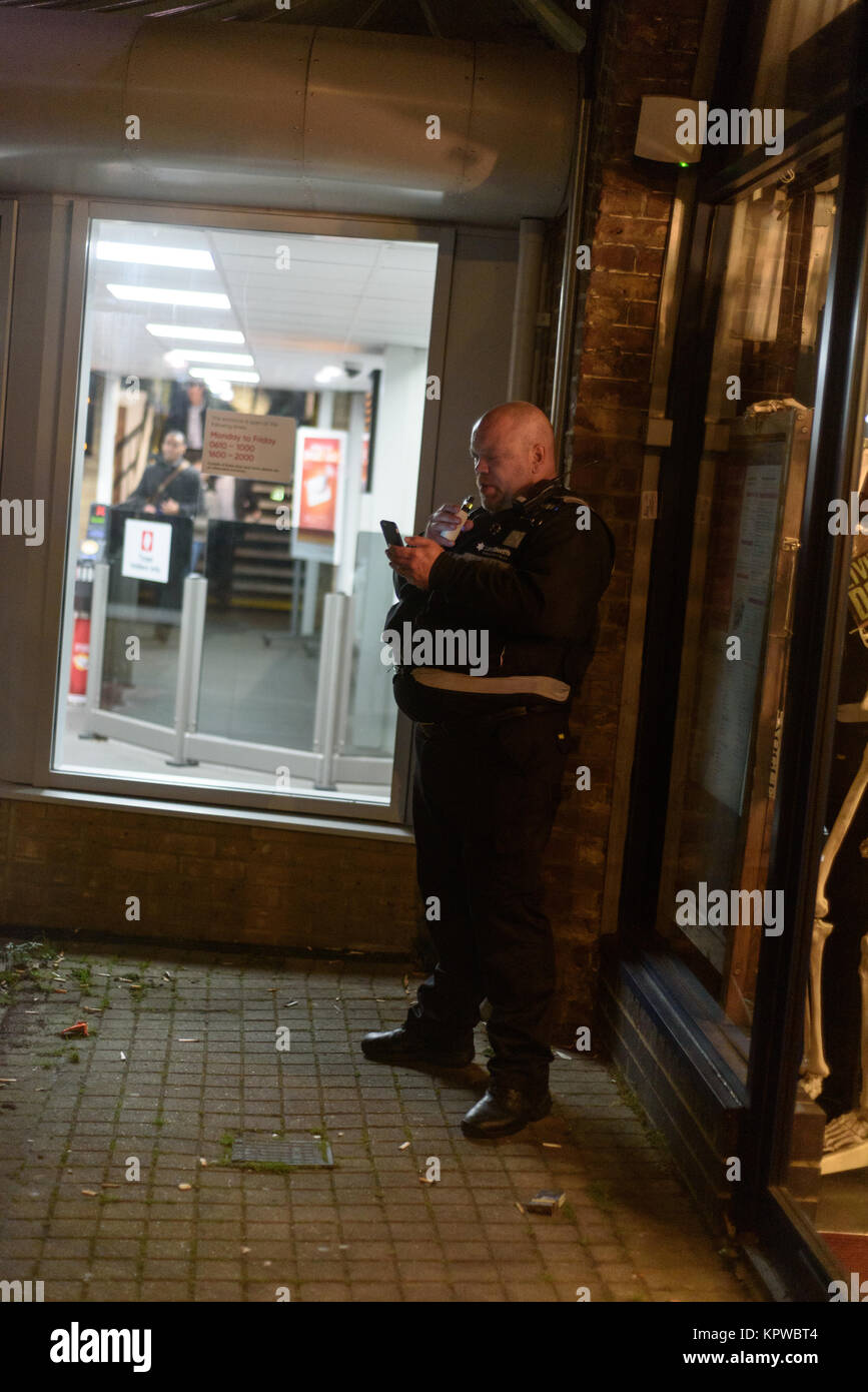 Land Sherriff, a form of private security, stands outside a station checking his phone and preparing to inhale a - Stock Image