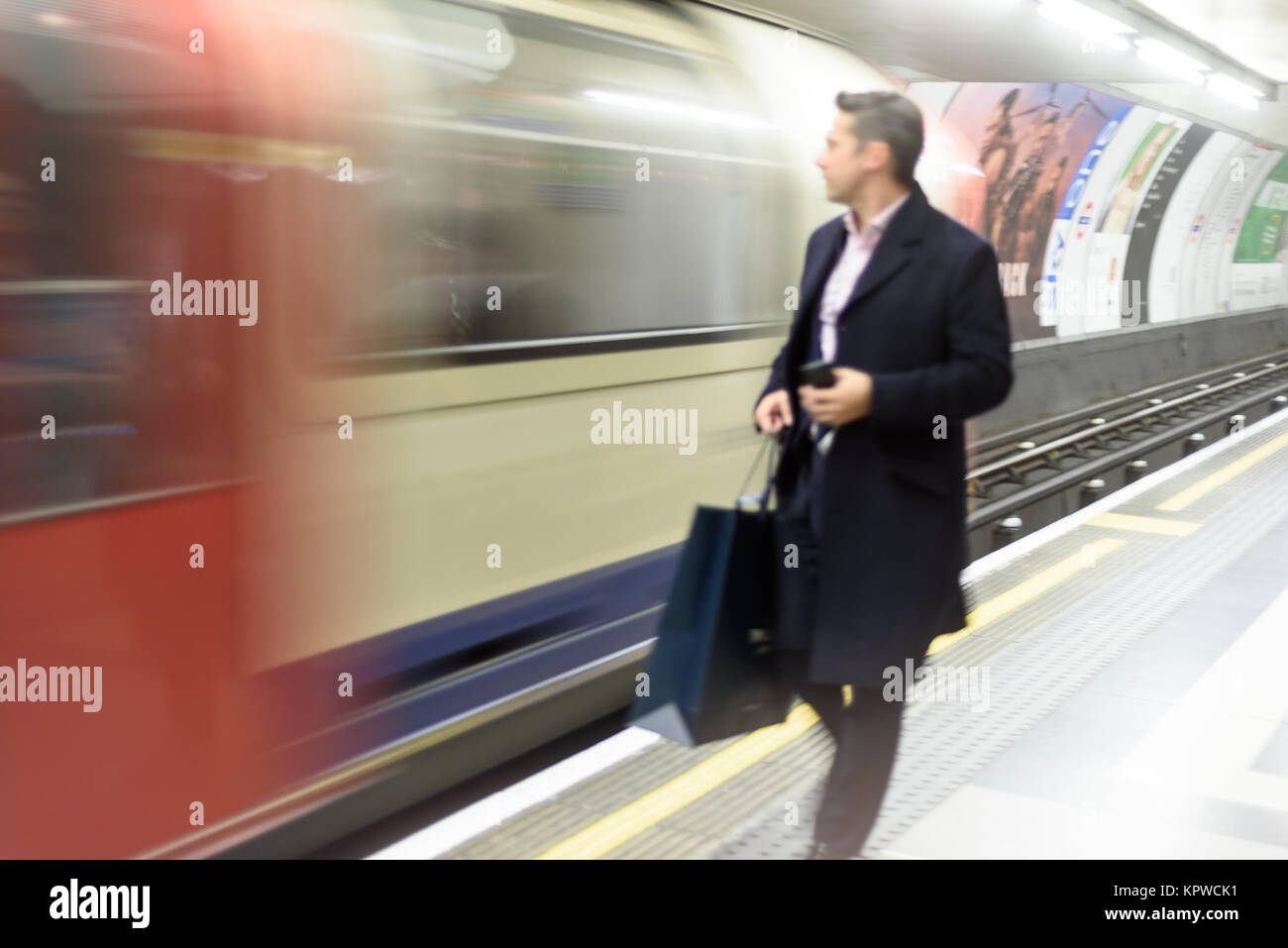 Intentional blurred motion blur of people using London Underground trains as the tube for public transport - Stock Image