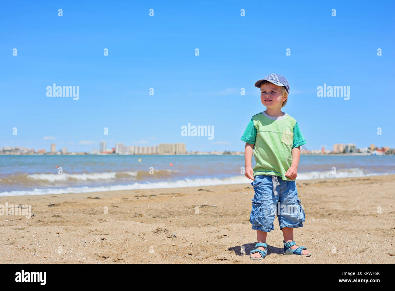 Cute small boy standing on the beach - Stock Image