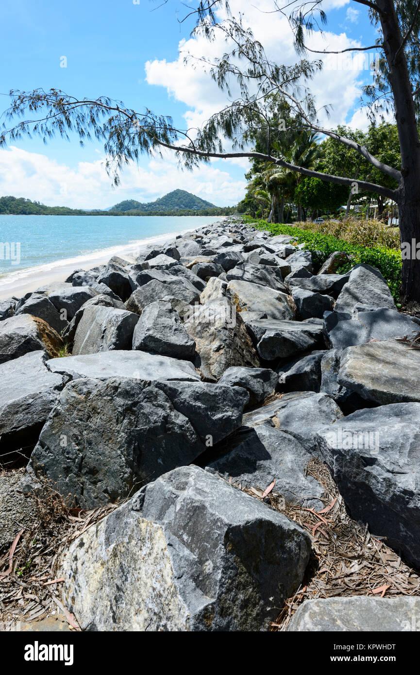 Rock breakwall at Clifton Beach, a popular Northern Beaches suburb of Cairns, Far North Queensland, FNQ, QLD, Australia - Stock Image