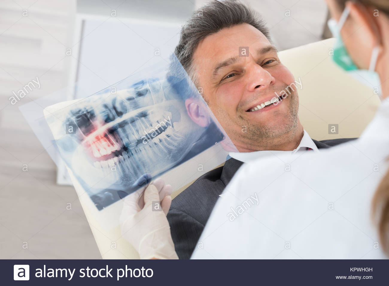 Dentist With Teeth X-ray In Front Of Businessman - Stock Image