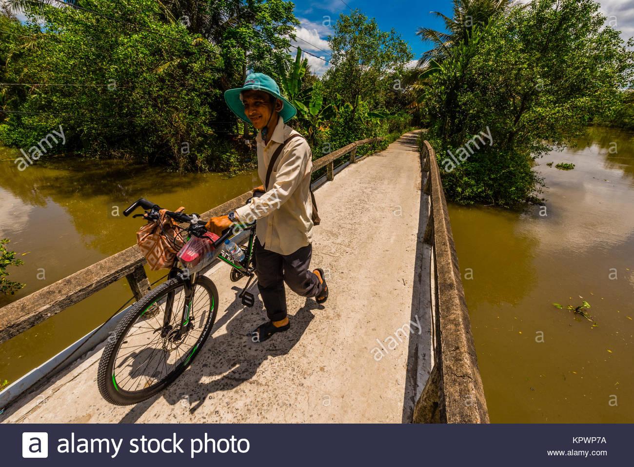 A man bicycling along the backwaters, Cai Lay, Mekong Delta, Vietnam. - Stock Image