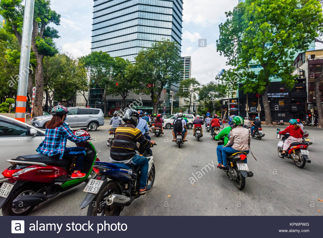Grab driver (motorcycle taxi), Two-wheeled traffic in Ho Chi Minh City (Saigon), Vietnam. There are over four million - Stock Image