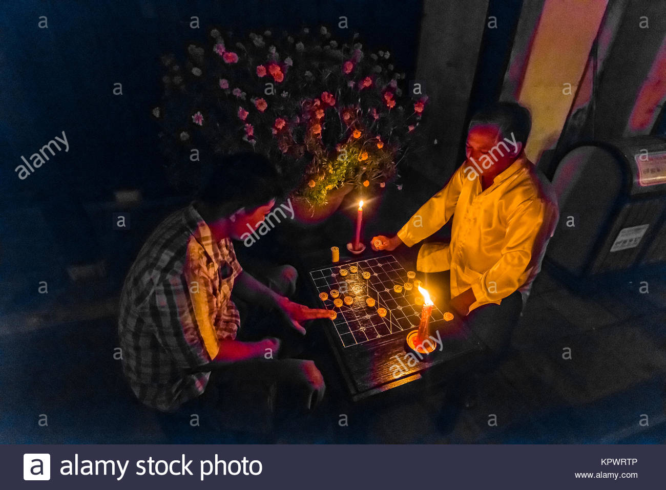 Men playing checkers by candlelight during the monthly Hoi An Full Moon Lantern Festival, Hoi An, Vietnam. - Stock Image
