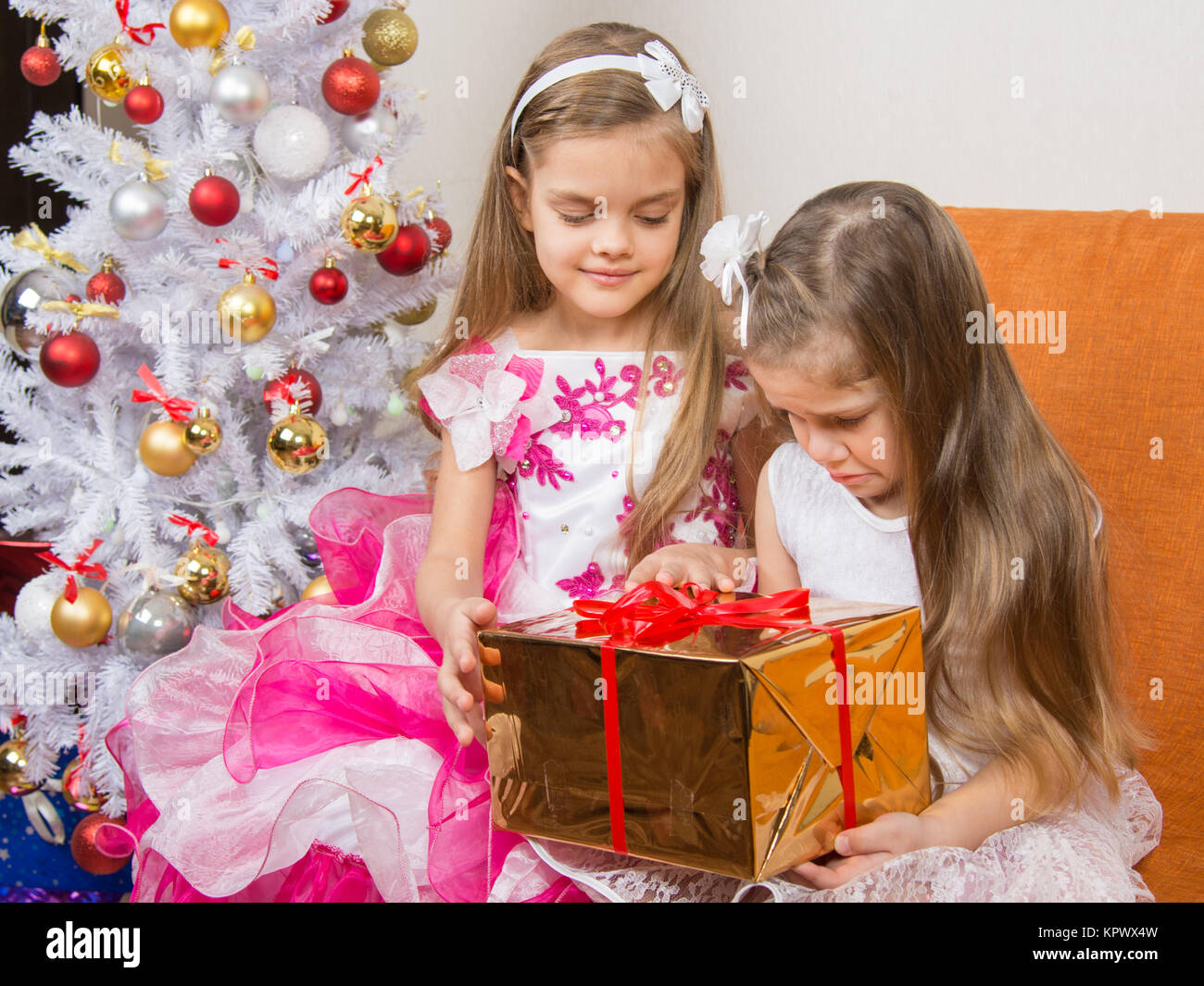 The older girl gives younger unwanted gift - Stock Image