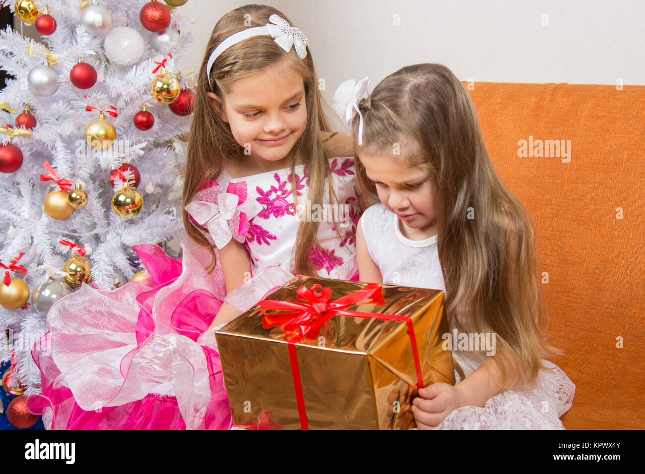Girl encourages another girl who gave the wrong gift - Stock Image