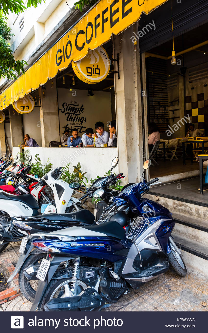 People relax in a sidewalk cafe as motorbikes crowd the sidewalk outside. Ho Chi Minh City (Saigon), Vietnam. There - Stock Image