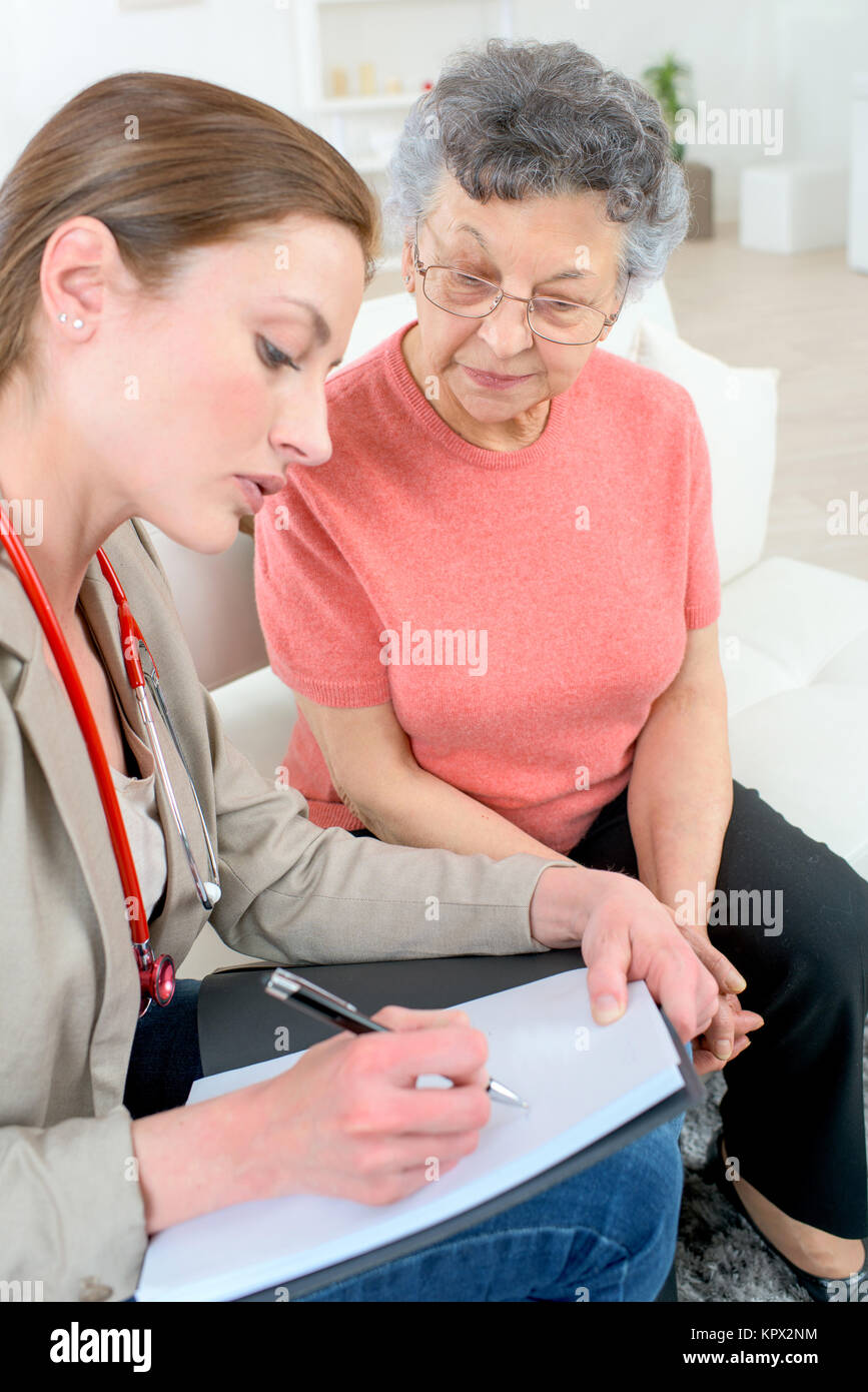Doctor writing a prescription for a senior patient - Stock Image