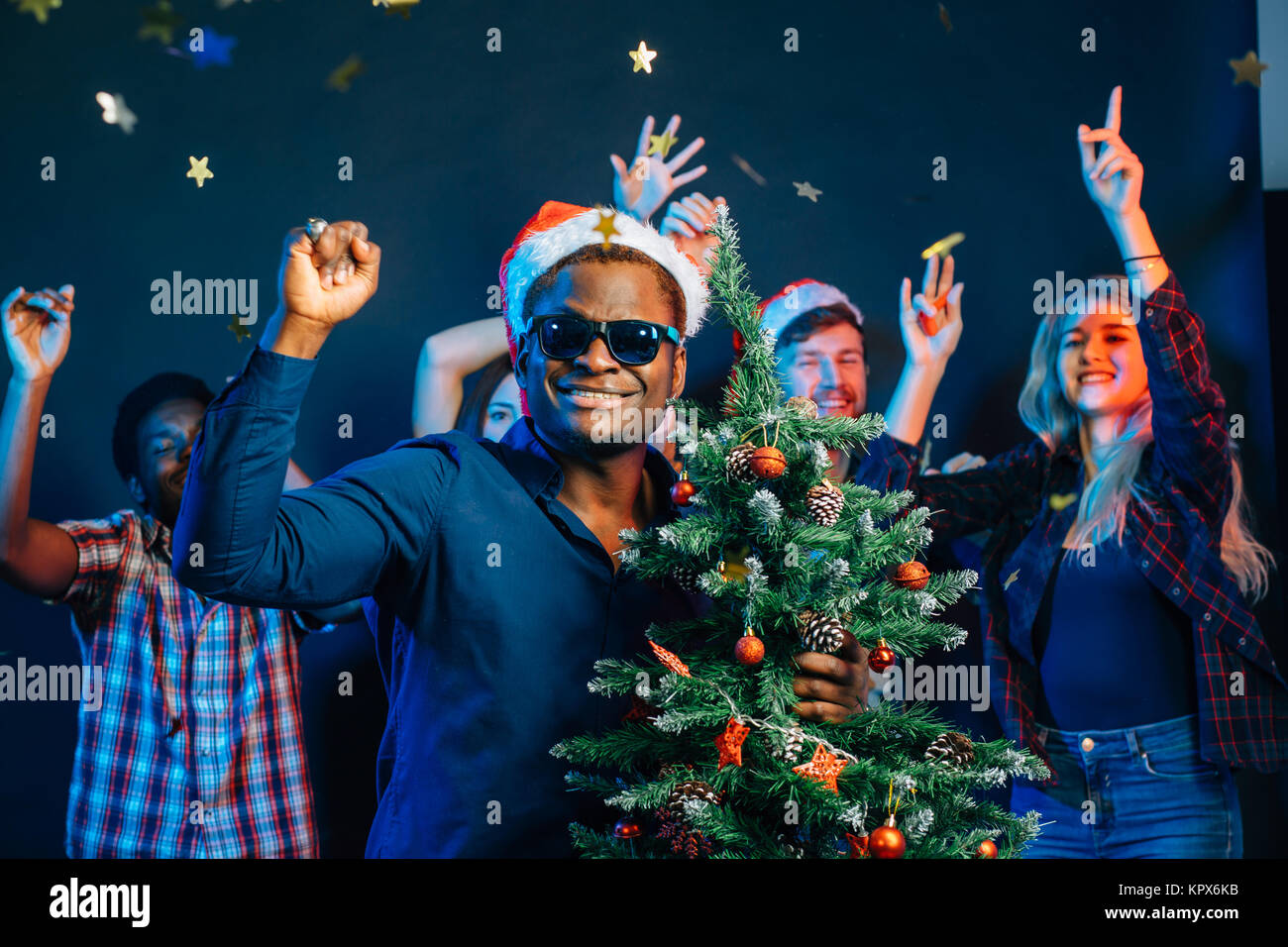 african american man hugging with cristmas tree - Stock Image