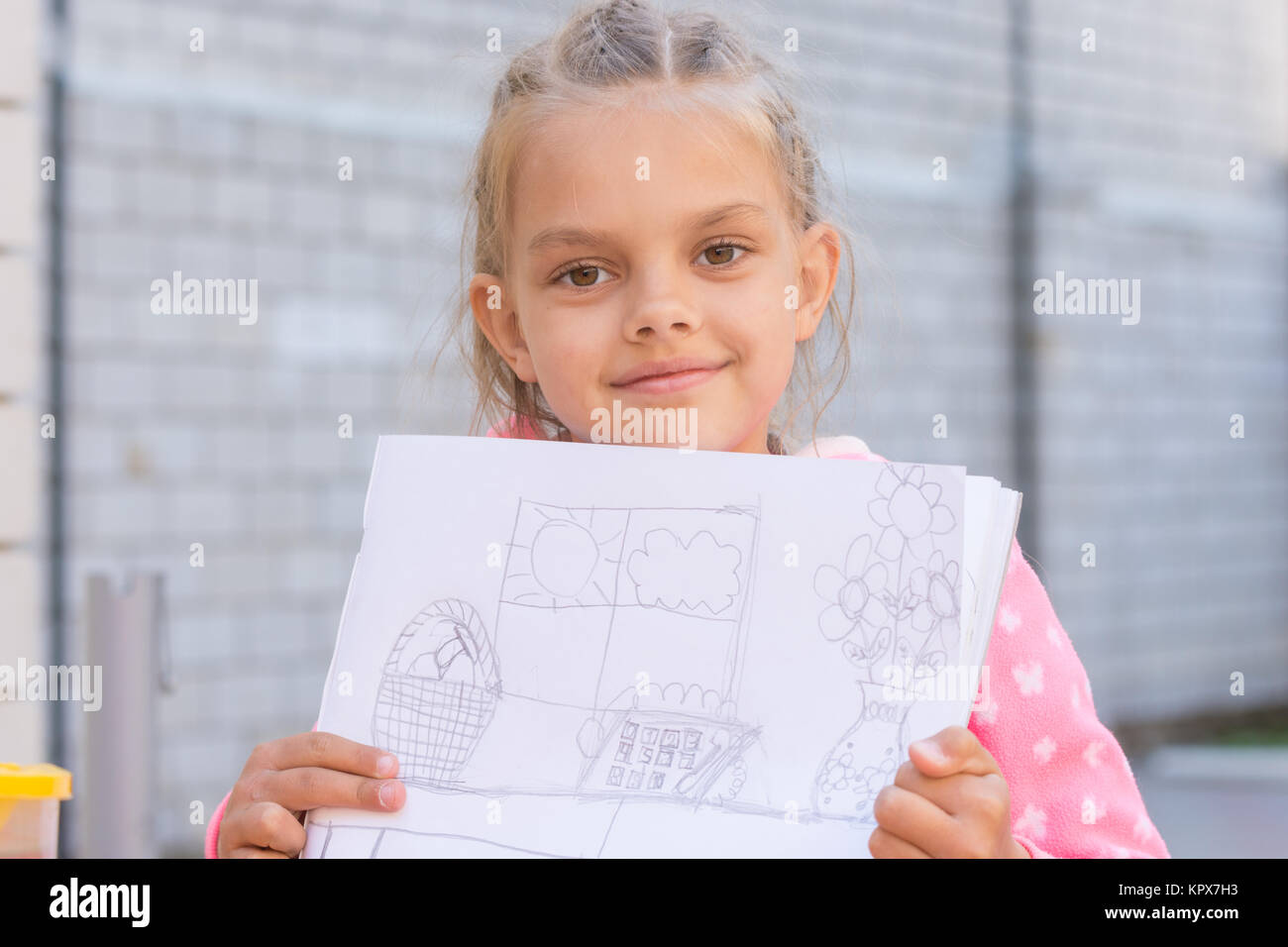 A girl shows a drawing, drawn in pencil - Stock Image