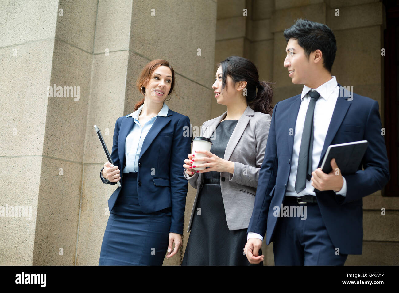 Group of business people walking out of office - Stock Image