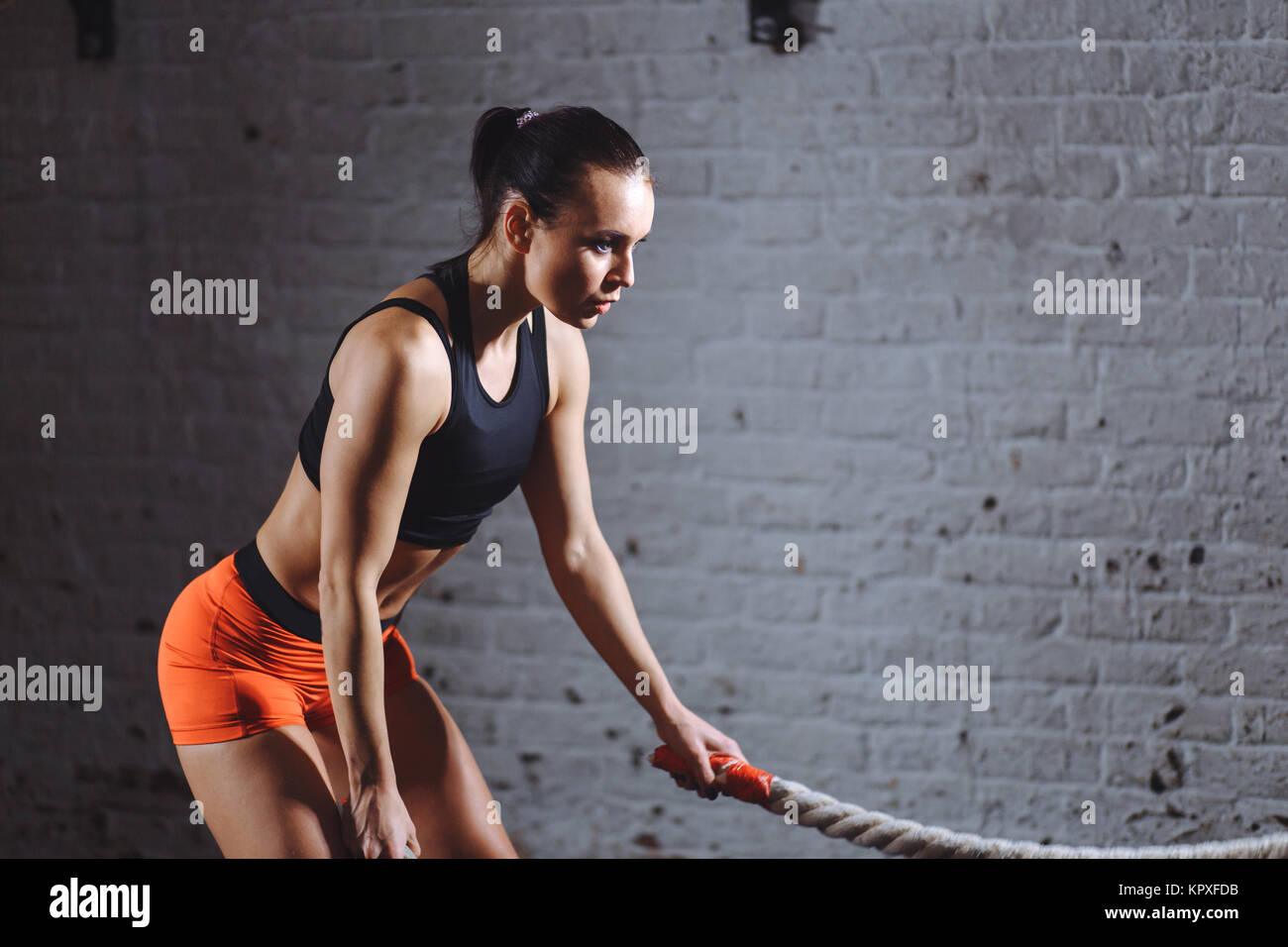 close up photo of Athletic woman doing battle rope exercises at gym - Stock Image