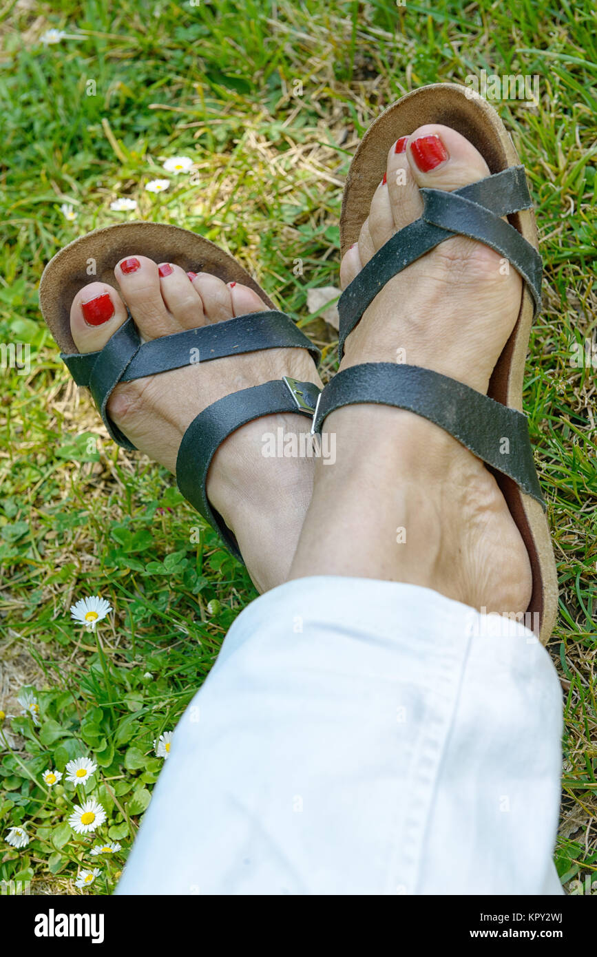 woman feet with red nails on grass background - Stock Image