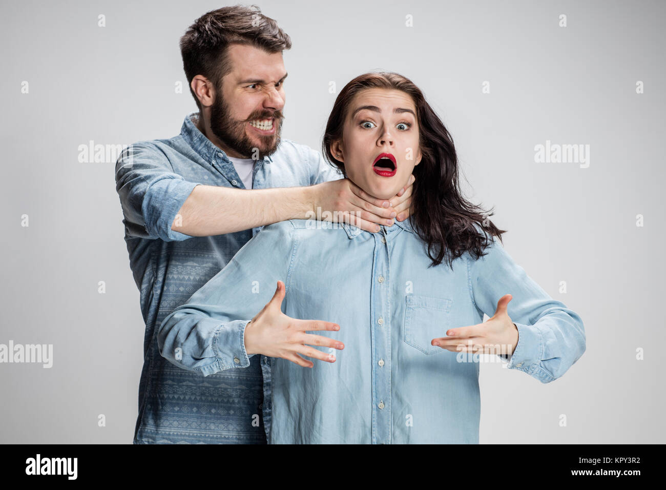 The quarrel men and women. Man strangling a woman on gray background - Stock Image