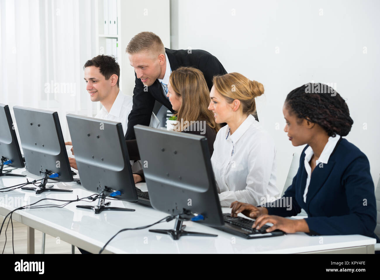 Businessman Helping His Colleagues In The Office - Stock Image