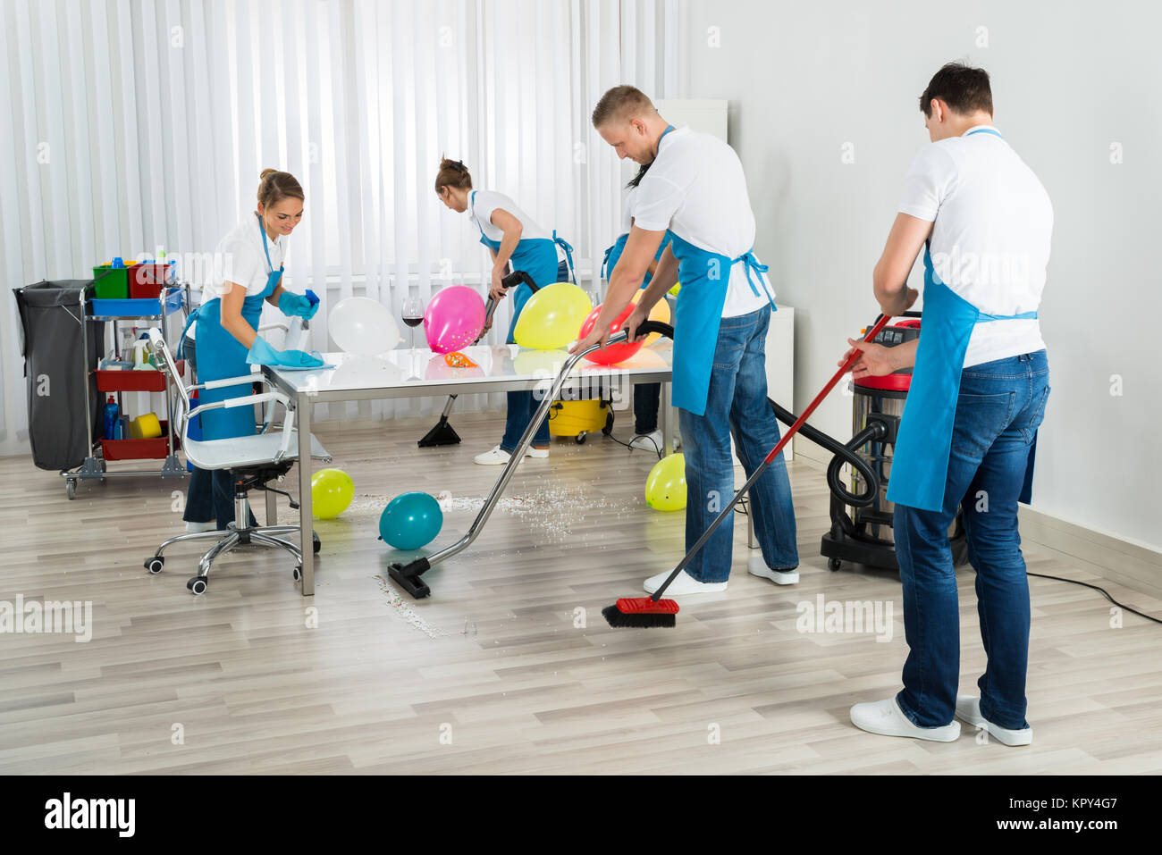 Janitors Cleaning The Office After Party - Stock Image