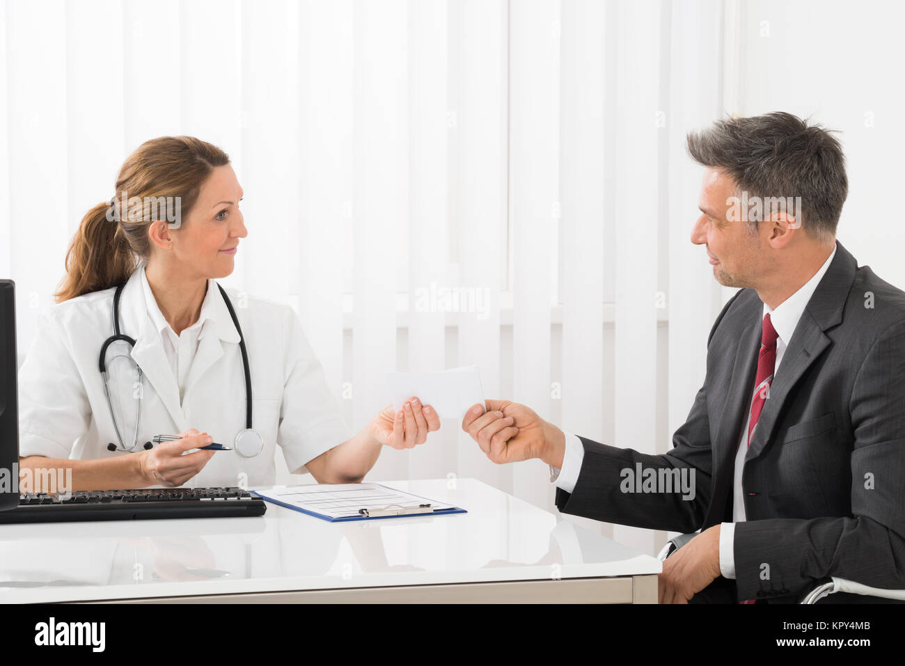 Doctor Giving Prescription To Businessman - Stock Image