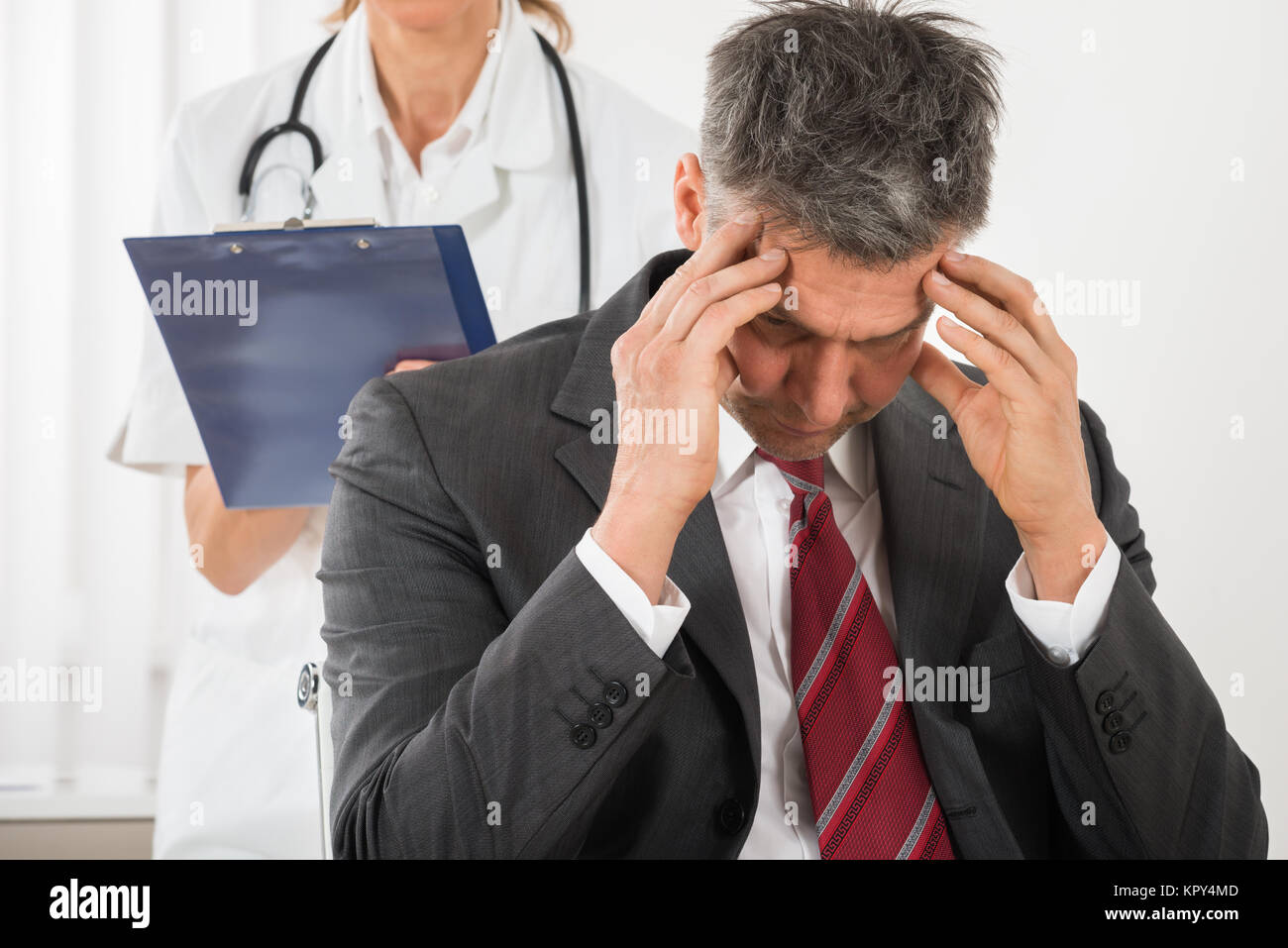 Doctor Standing Behind The Businessman Having Headache - Stock Image