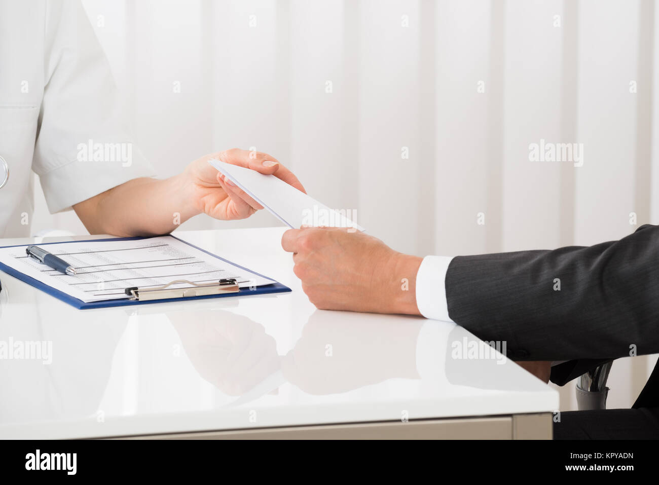 Doctor Hand Giving Prescription To Businessman Stock Photo