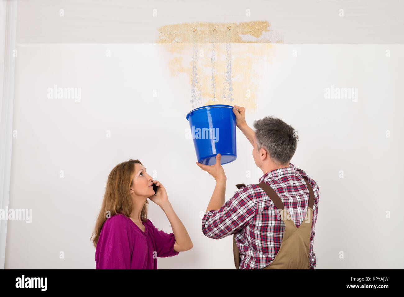 Worker Collecting Water In Bucket From Ceiling - Stock Image