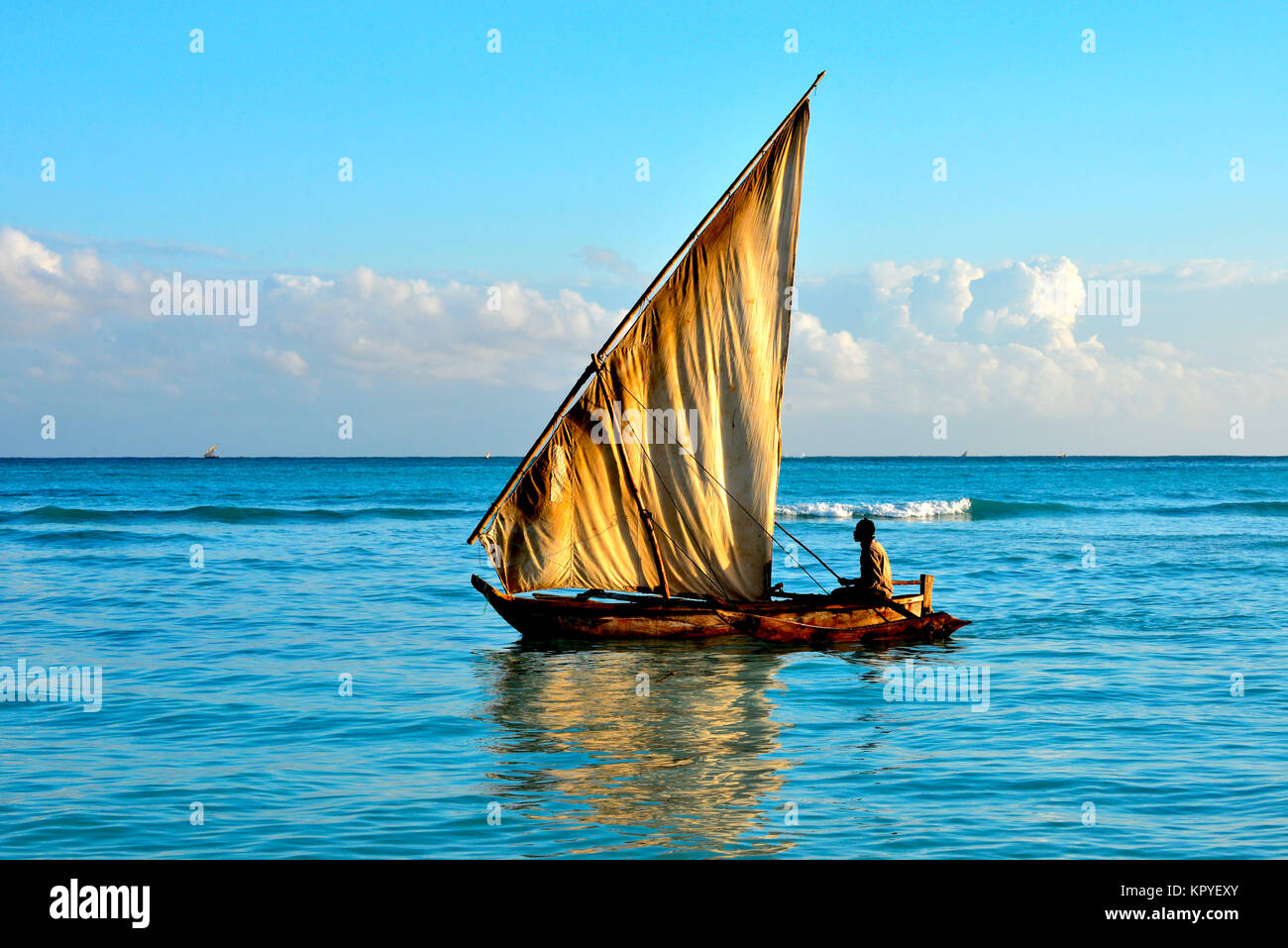 Sunrise by the sea in Zanzibar, tropical island paradize of Tanzania. Yacht on water. - Stock Image