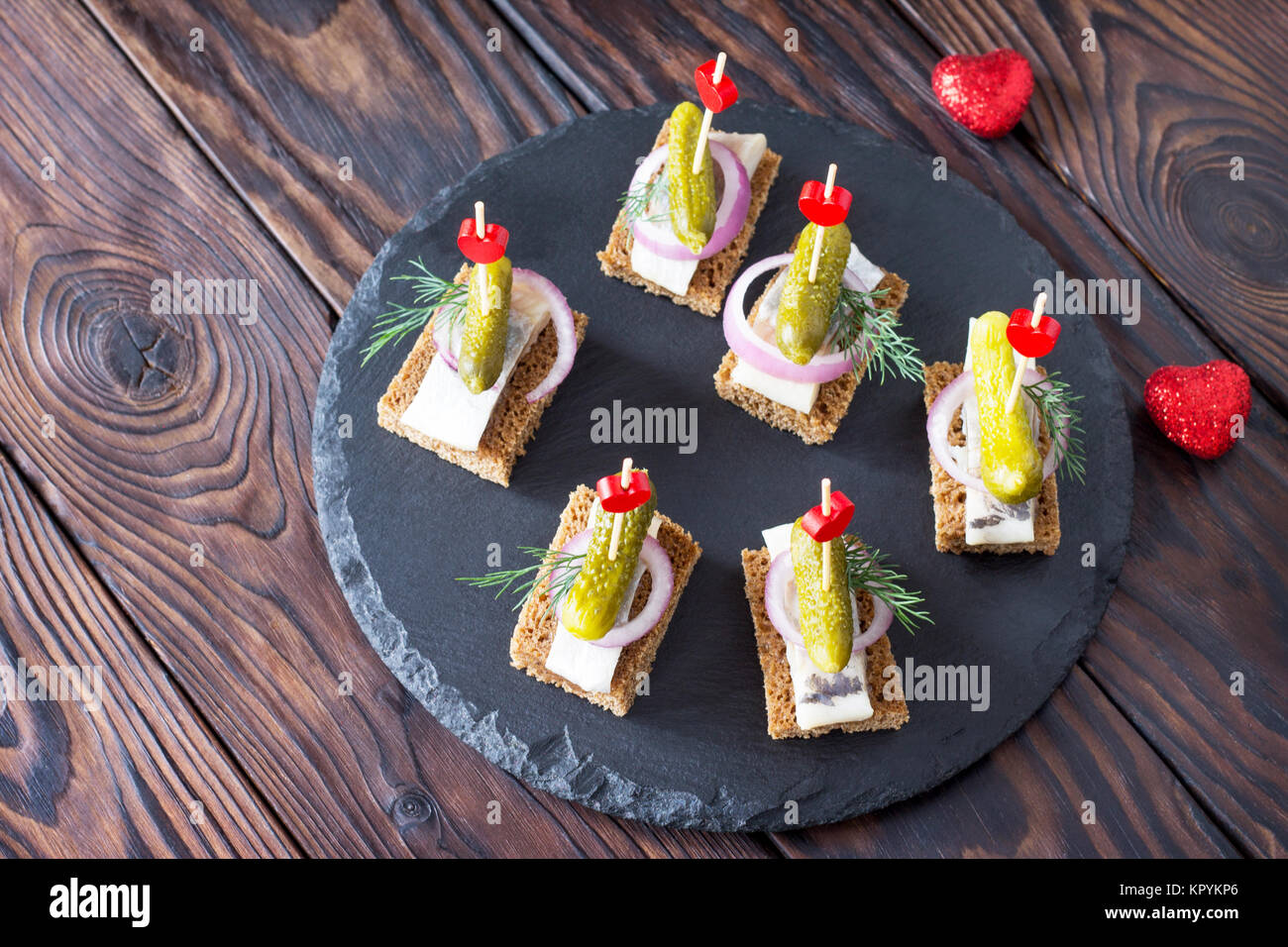 Canapes with rye bread, herring and pickles on a festive table. Valentine's day concept or wedding. - Stock Image