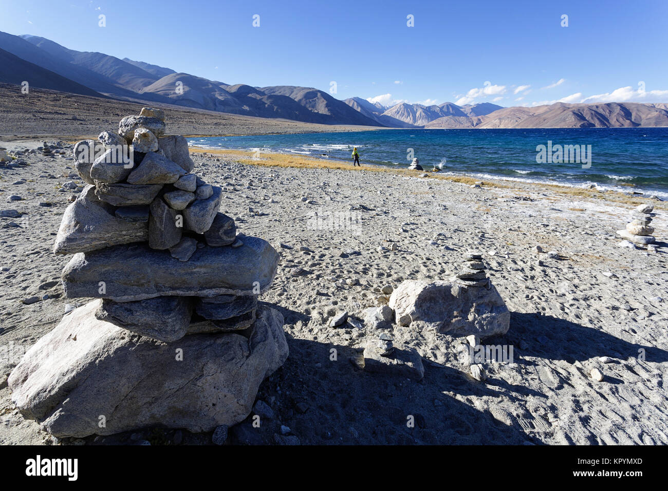 Young caucasian boy playing at stone towers by the Pangong Tso lake in windy conditions, Ladakh, Jammu and Kashmir, Stock Photo