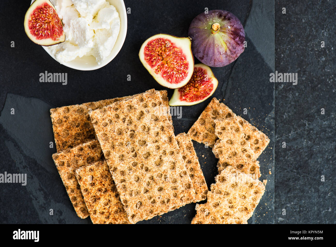 Wholegrain rye crispbread crackers, figs and ricotta cheese are ready for the healthy snack, dark background - Stock Image