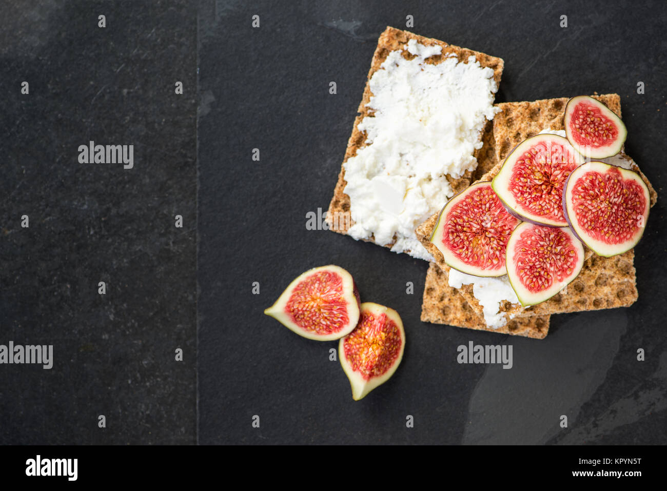 Healthy snack from wholegrain rye crispbread crackers, figs and ricotta cheese on dark slate board - Stock Image