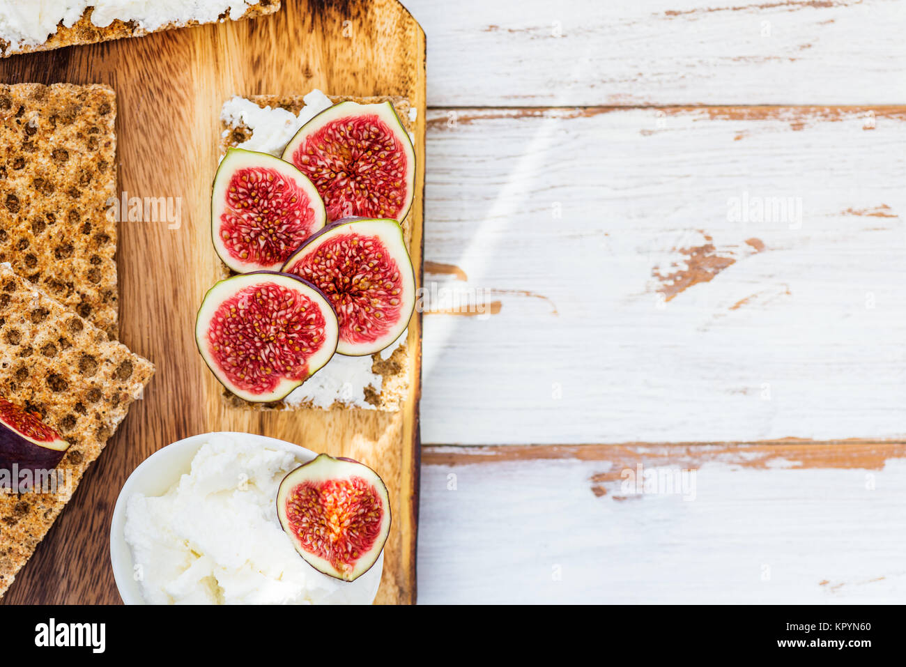 Healthy snack from wholegrain rye crispbread crackers, figs and ricotta cheese on light wooden background - Stock Image