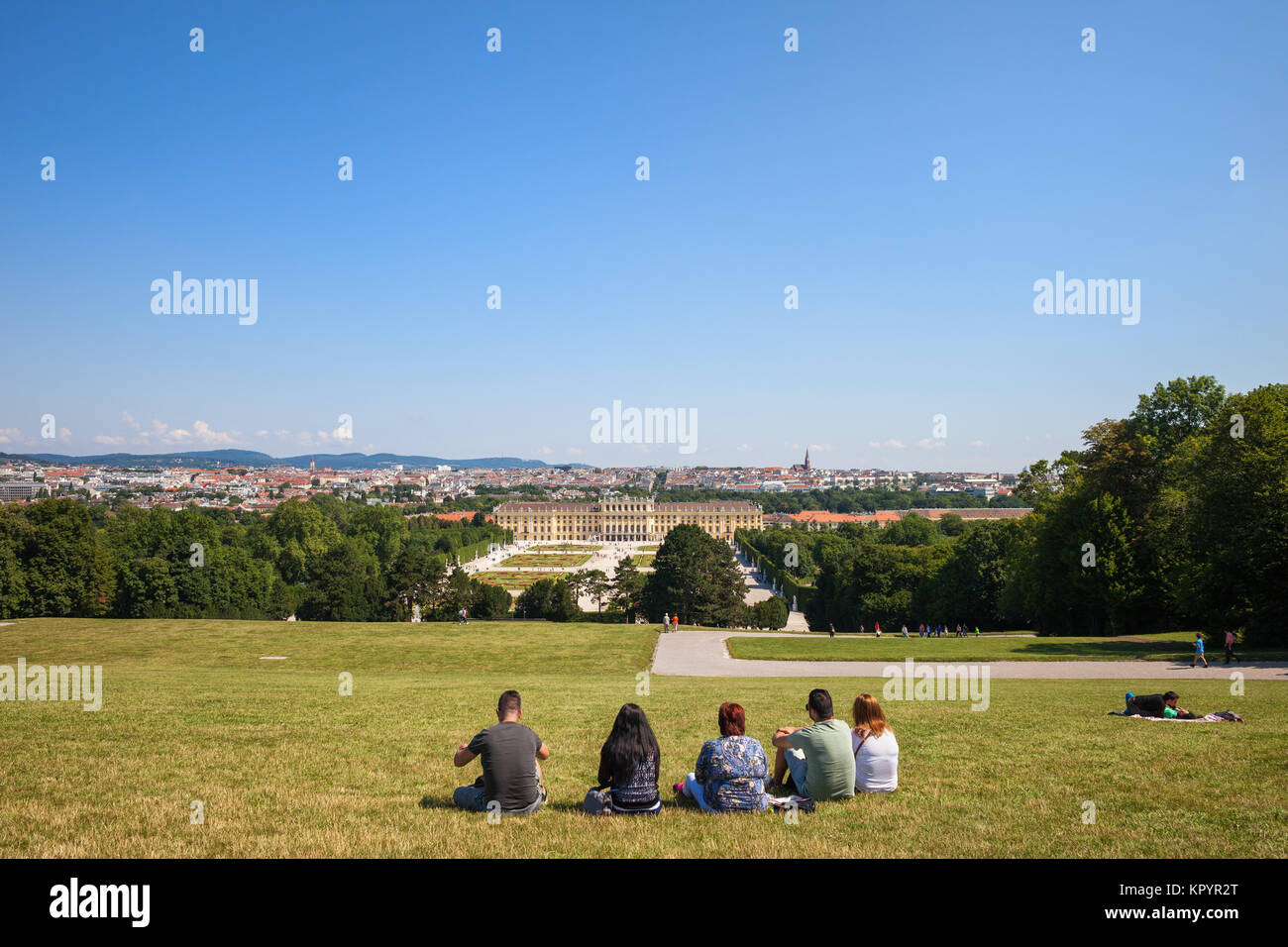 Group of people sitting on grass overlooking the Schonbrunn Palace and Vienna city from Schonbrunn park hill in - Stock Image