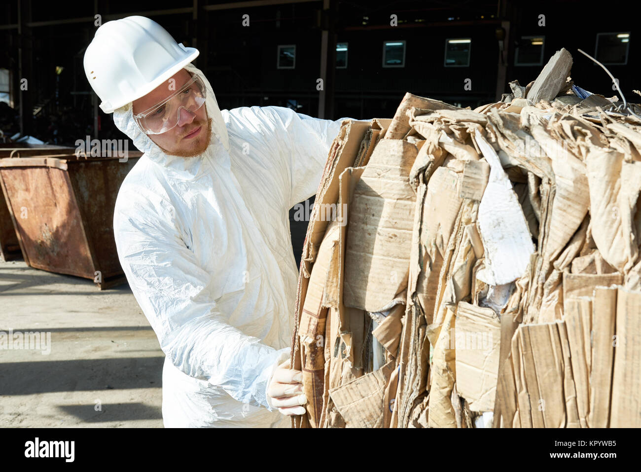 Worker in Hazmat Suit Sorting Cardboard at Recycling Factory Stock Photo