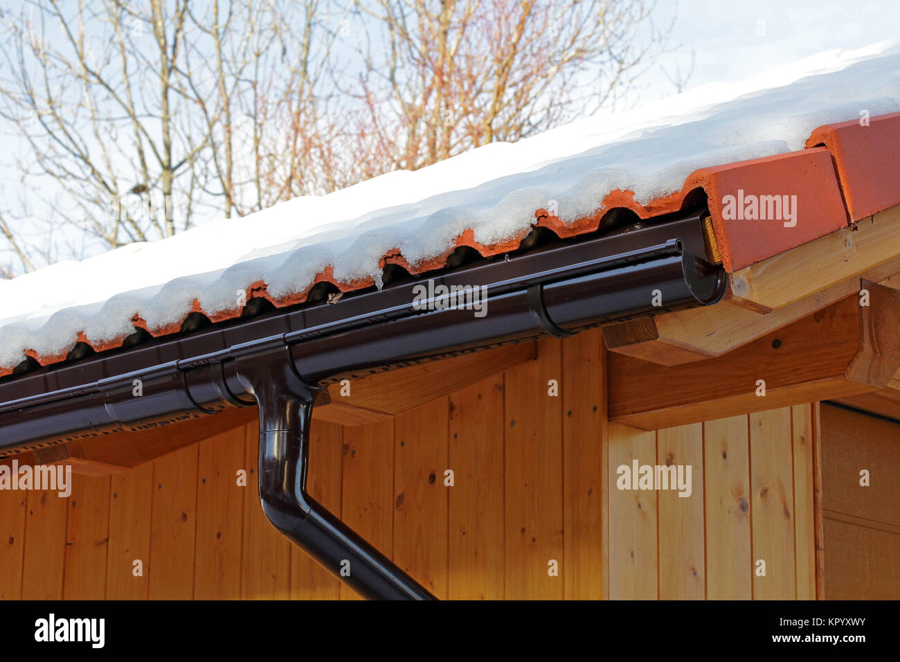 a wooden roof with rain gutter and drainpipe in winter - Stock Image