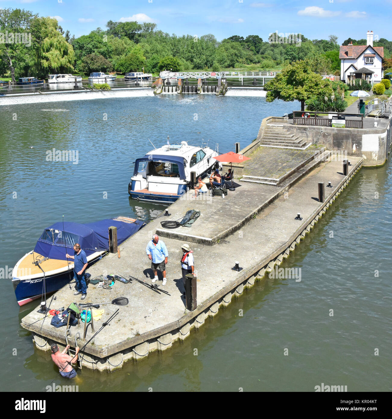 Looking down from above at approach to Goring Lock on River Thames in Oxfordshire with fishermen & motor launch Stock Photo
