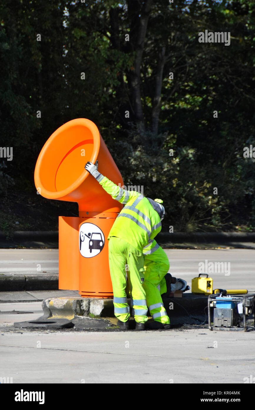 Workmen installing orange high level litter bins for use by both lorry & car drivers departing Lymm M6 motorway - Stock Image