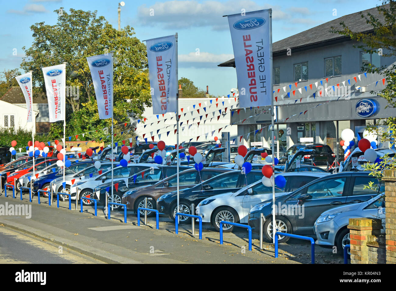 Balloons bunting & banners promoting & advertising by a Ford main car dealer holding supersale of used secondhand - Stock Image