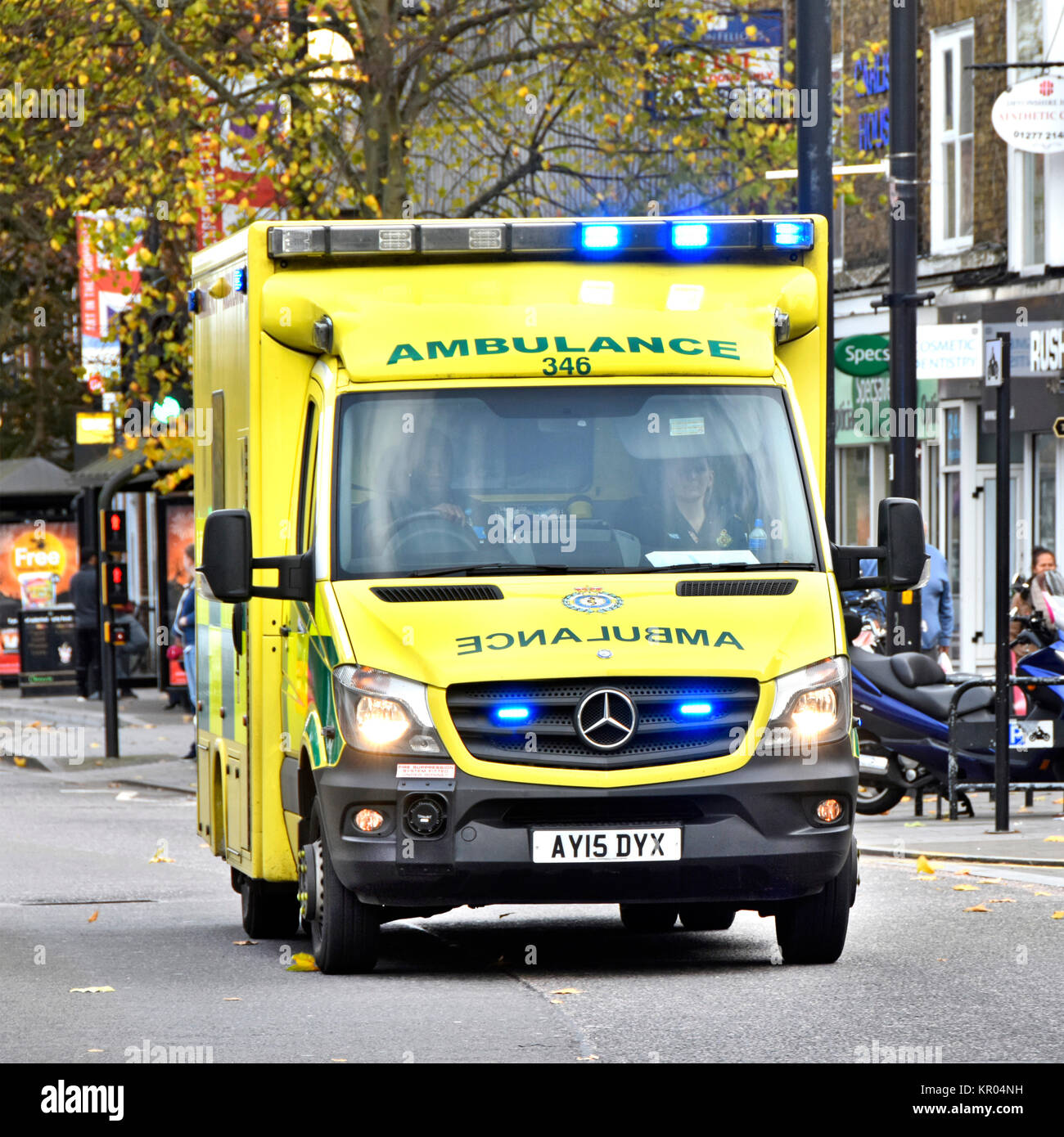 East of England Emergency Ambulance Service NHS vehicle & crew on 999 journey along Brentwood Essex shoppers - Stock Image
