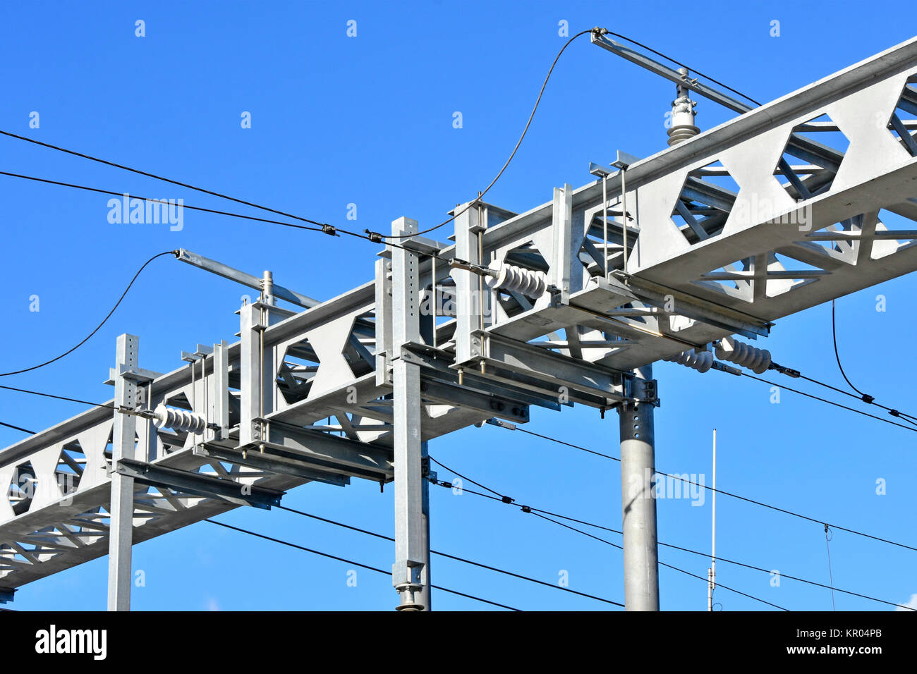 Twin castellated steel beams in gantry for overhead electricity cables powering electric trains on main line railway - Stock Image