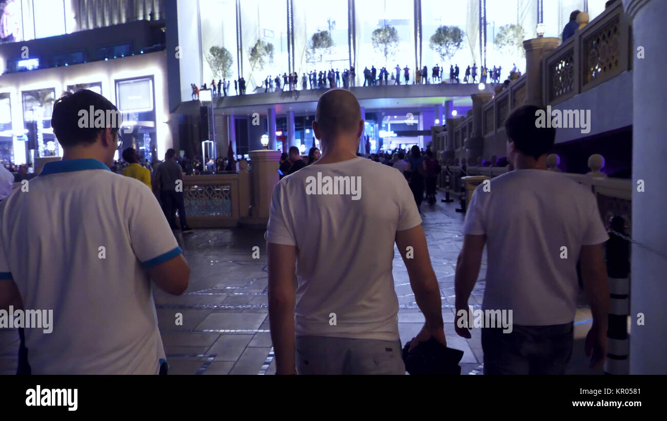 America, New YorkRear - 18 MAY, 2017: Rear view of three men walk in the city at night. Back view of businessman - Stock Image