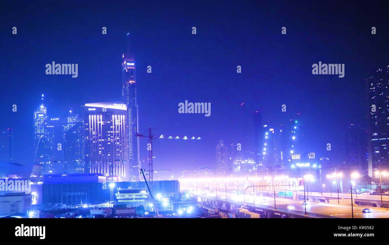 Big city traffic. highway and traffic in city at night. City skyline with multiple flyovers over full moon. Busy - Stock Image